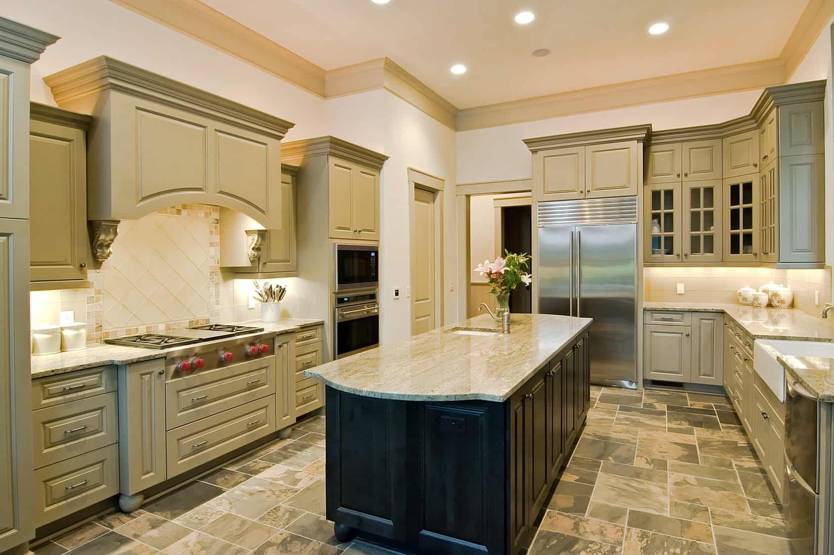 Recessed ceiling lights illuminate this kitchen featuring a dark wood island bar over limestone flooring. It is surrounded by stainless steel appliances and beige cabinetry against the white walls.