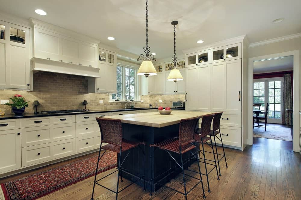 Wicker counter chairs sit at a black breakfast island that's illuminated by a pair of dome pendant lights. It is accompanied by a red printed runner and white cabinetry against the brick backsplash.