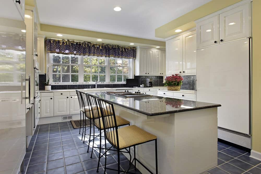 Sleek kitchen with black tiled flooring and white framed windows dressed in a dotted valance. It includes white cabinetry and a matching island bar lined with cushioned metal chairs.