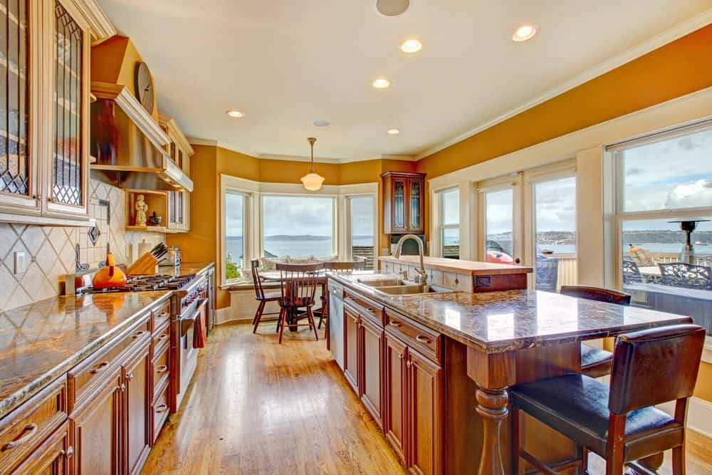 Warm kitchen with wooden cabinetry and a matching breakfast island paired with black cushioned chairs. It has rich hardwood flooring and glass paneled windows overlooking a stunning outdoor view.