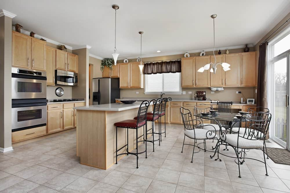 A quartz top kitchen island lined with black metal counter chairs matches the light wood cabinetry against the beige walls. It is accompanied by stainless steel appliances and an ornate metal dining set lighted by a unique chandelier.