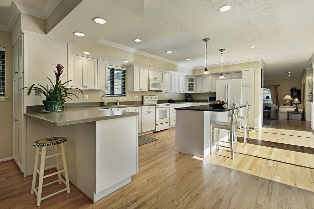 An open kitchen with white appliances and cabinetry matching with the breakfast island that's paired with light wood counter chairs. It is illuminated by glass dome pendants and recessed ceiling lights.