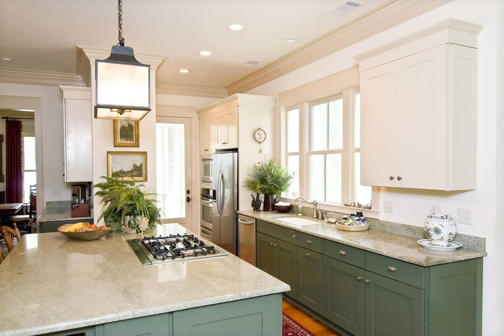 Galley kitchen with white upper cabinets and green lower cabinets topped with granite counters. It has hardwood flooring and white framed windows allowing natural light in.