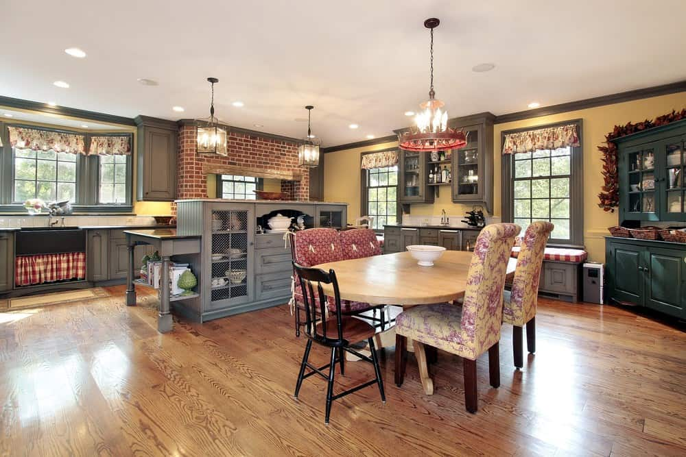 Country style kitchen with emerald green cabinet and a sky blue breakfast bar lighted by cube pendants. It includes window seat nooks and a light wood dining table surrounded by mismatched chairs.