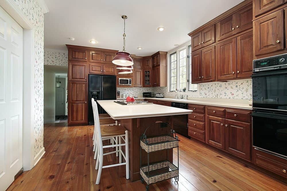 Floral wallpaper sets a charming backdrop to the wooden cabinetry in this kitchen with black appliances and a quartz top island lined with red dome pendants and white counter chairs.