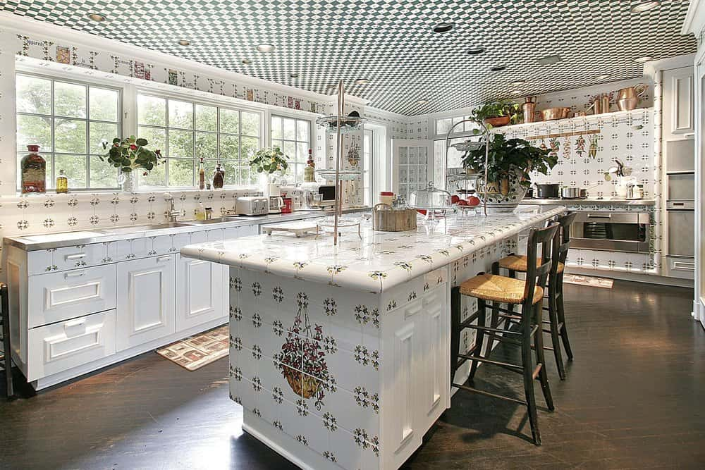 Patterned decorative backsplash tiles complement the island bar that's topped with tiered trays and a large potted plant. This kitchen has dark hardwood flooring and a striking checkered ceiling mounted with recessed lights.