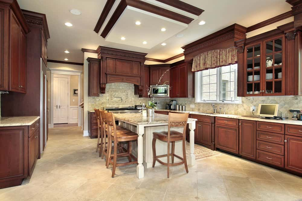Classic kitchen with dark wood cabinetry and a granite top island surrounded by wooden counter chairs. It has a drop ceiling and white framed windows dressed in a floral valance.