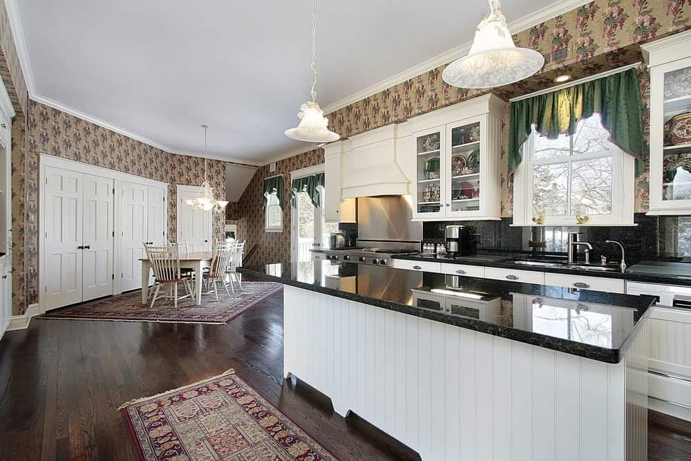 Clad in floral wallpaper, this kitchen features white cabinetry and a beadboard island bar topped with a black granite counter. It is illuminated by charming dome pendants along with natural light from the white framed window that's dressed in a green valance.