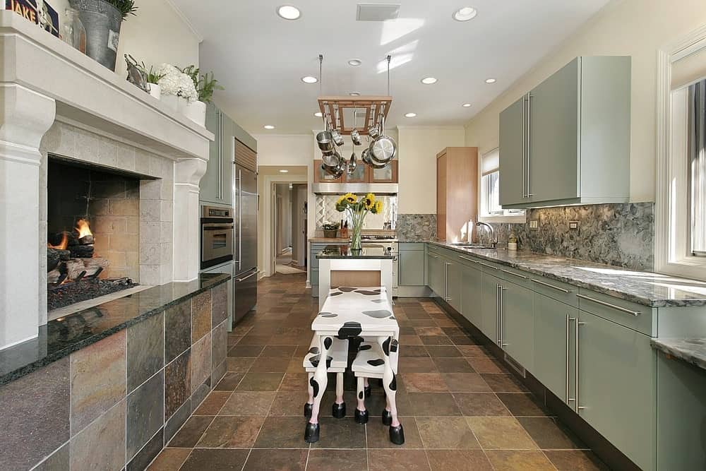 Country style kitchen offers sage green cabinetry and a wooden pot rack that hung over the island bar attached with a cow designed eating counter. It includes stainless steel appliances and a brick fireplace fixed against the beige wall.