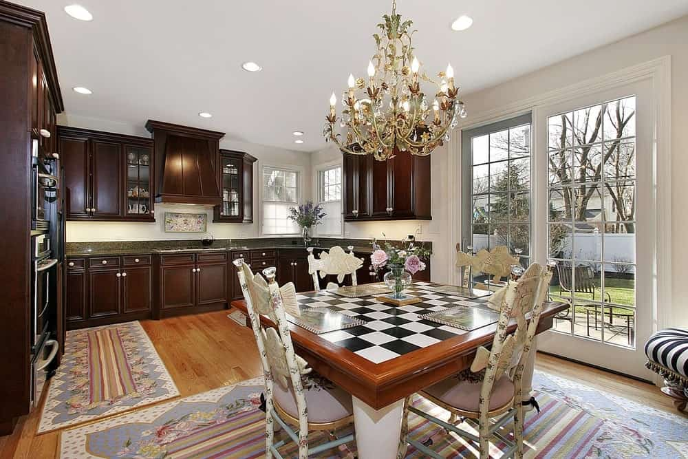 A fabulous chandelier illuminates the charming dining set that sits on a floral rug over the hardwood flooring. This kitchen boasts dark wood cabinetry and a glazed slider leading out to the lush green yard.
