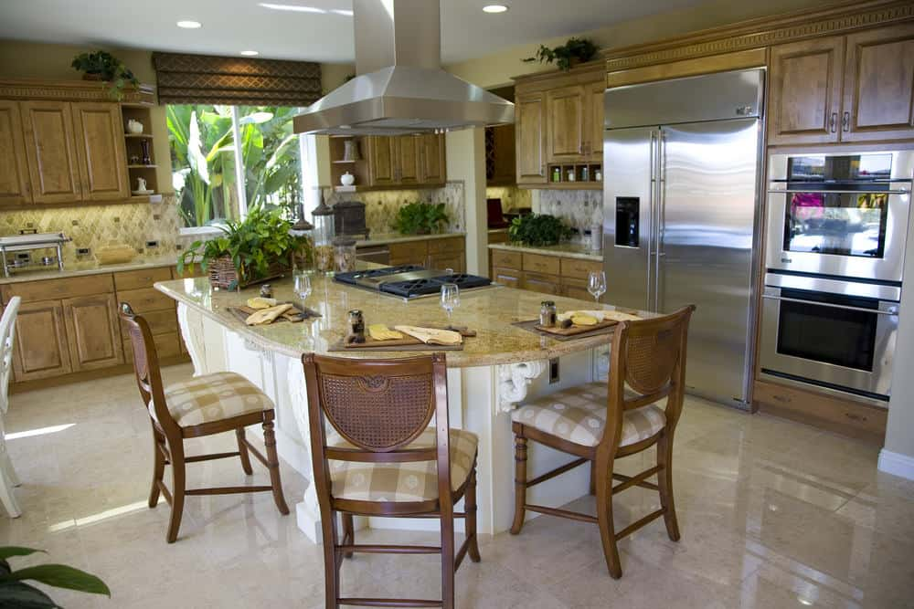 Wooden cushioned chairs sit at a white kitchen island that's topped with a granite counter and built-in cooktop. It is surrounded by natural wood cabinetry and stainless steel appliances.