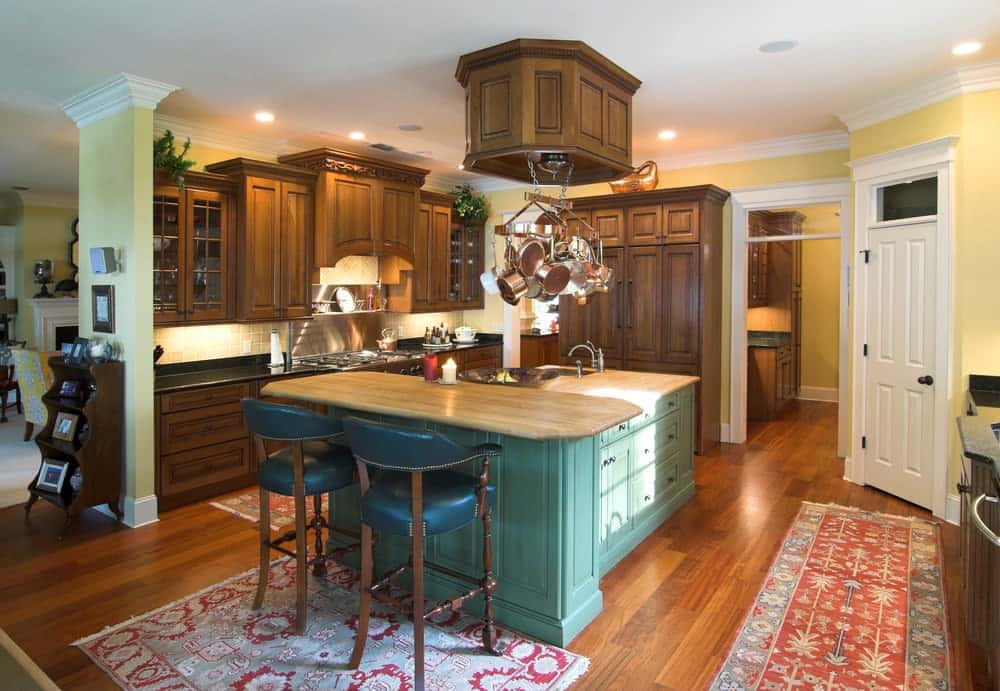 This kitchen features wooden cabinetry and a green breakfast island paired with cushioned bar stools. It includes a copper pot rack and red printed rugs that lay on the rich hardwood flooring.