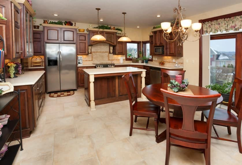 An eat-in kitchen with a wooden dining set and cabinetry matching with the quartz top island. It has limestone flooring and brick backsplash that blends in with the beige walls.