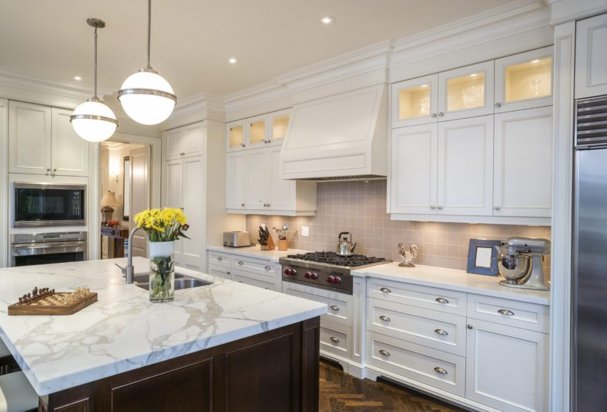 White cabinetry surrounds a dark wood breakfast island that's topped with a marble counter and dual sink. It is illuminated by glass globe pendants and recessed ceiling lights.