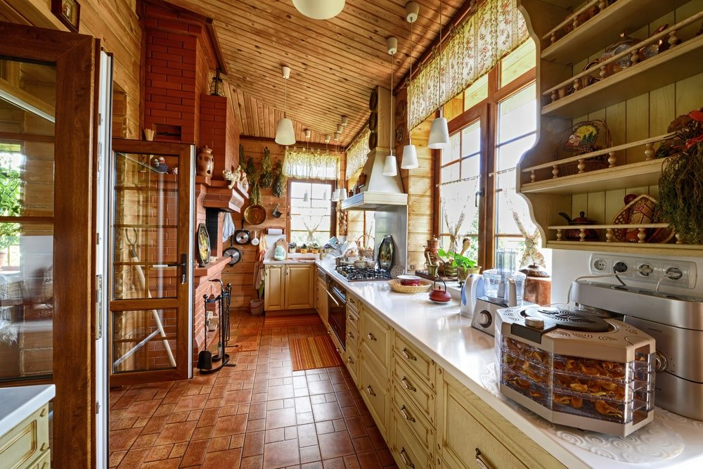This is an over-all charming and homey Country-style kitchen that has terracotta flooring tiles that complement the long beige cabinetry of the L-shaped kitchen peninsula. Across from this is the red brick fireplace with bricks reaching up all the way to the wooden shed ceiling.