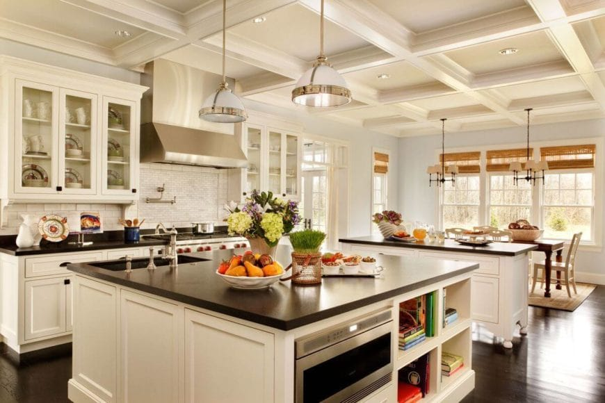 This is a bright and white Country-style kitchen contrasted by the dark hardwood flooring and the black countertops of the two kitchen islands and the small peninsula. The highlight of this kitchen is the gorgeous white tray ceiling that elevates the elegance of this large room.