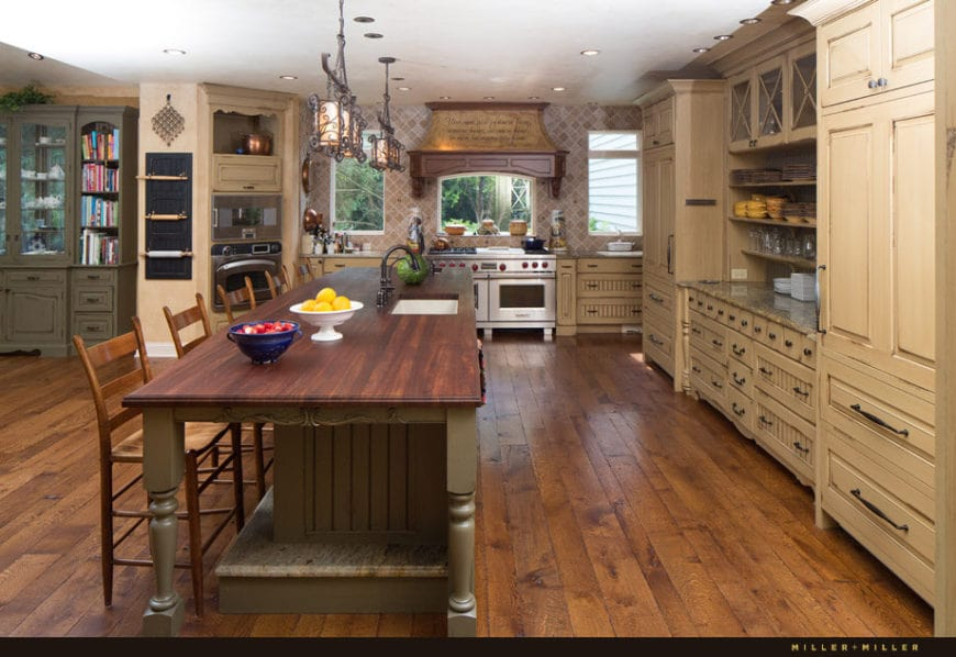 The earthy tone of the cabinetry in this Country-style kitchen is a nice complement to the hardwood flooring. It also matches with the patterned wallpaper at the cooking area on the far wall. These are brightened by a white ceiling that hangs wrought iron lanterns over the kitchen island.