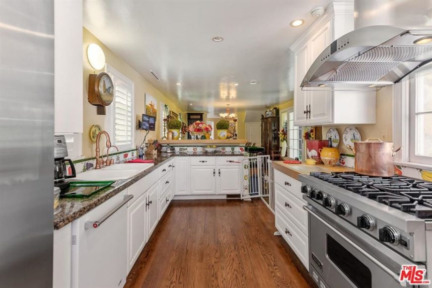 This small and cozy Country-style kitchen does not have enough space on its hardwood flooring for a kitchen island. It makes up for this with two kitchen peninsulas with one having an L shape. These peninsulas have white shaker cabinets and drawers is contrasted by the brown countertops.