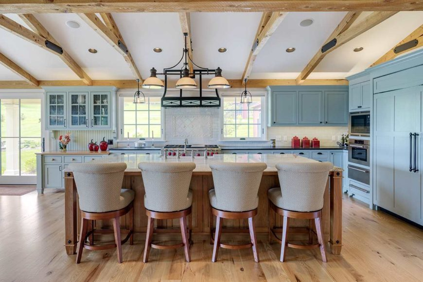 The white shed ceiling has exposed wooden beams that support a row of dome pendant lights over the wooden kitchen island that also serves as a breakfast bar for the gray cushioned chairs. This is given a nice background of a kitchen peninsula with light blue cabinetry.