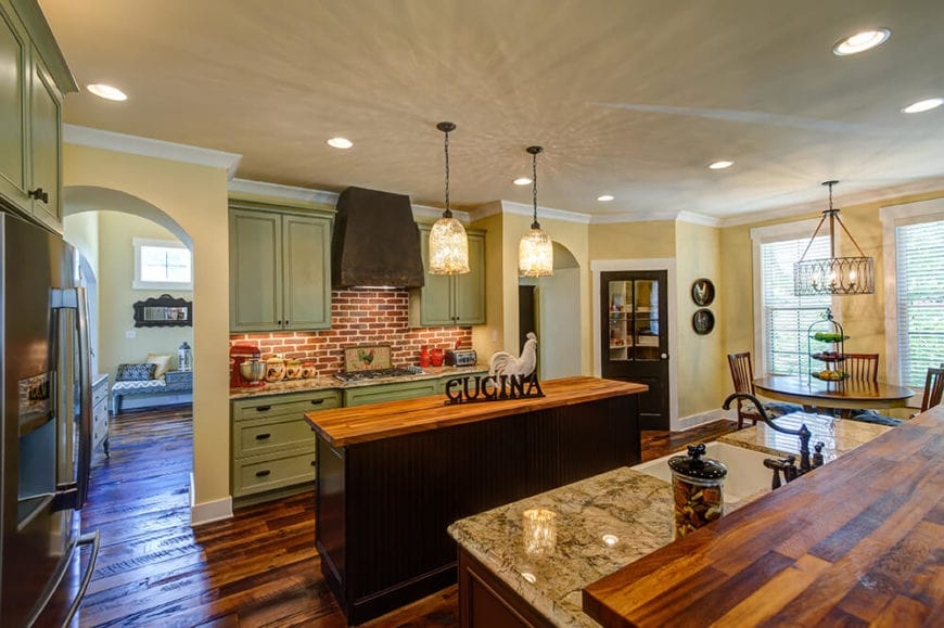 This charming Country-style kitchen has a couple of brilliant glass pendant lights hanging over the narrow wooden kitchen island with a butcher block countertop matching the hardwood flooring. This is then contrasted by the green cabinetry of the peninsula that has a red brick backsplash.