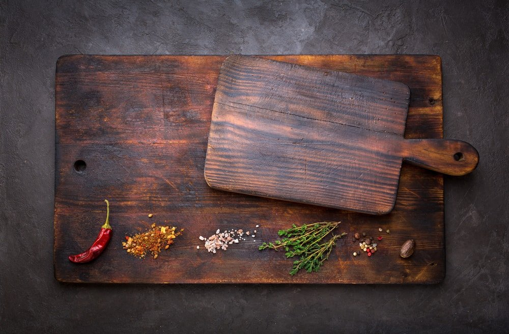 A small and a large wooden cutting boards with spices.