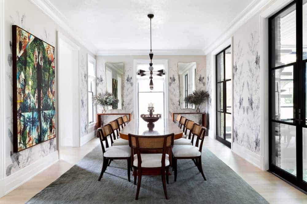 Colorful wall art provides a nice accent in this dining room with cushioned chairs and an oval dining table illuminated by a unique chandelier. It includes a pair of wooden console tables and rectangular mirrors that add perfect symmetry in the room.