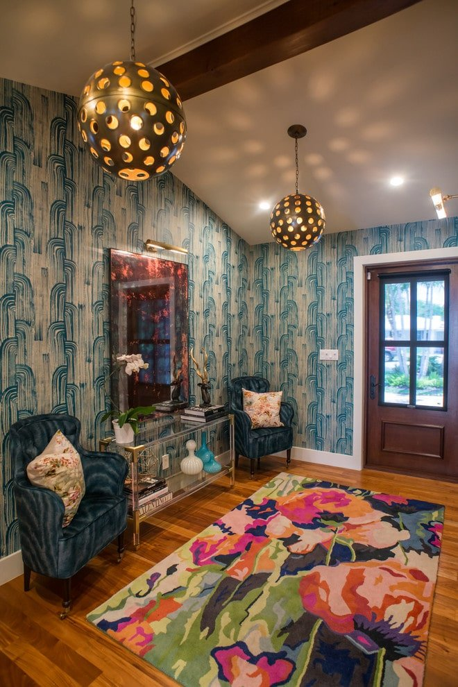 Clad in blue patterned wallpaper, this foyer boasts a colorful floral rug and gorgeous wingback chairs flanking the mirrored wall art and glass console table over the rich hardwood flooring. It is illuminated by a pair of perforated round pendants hanging from the cathedral ceiling.