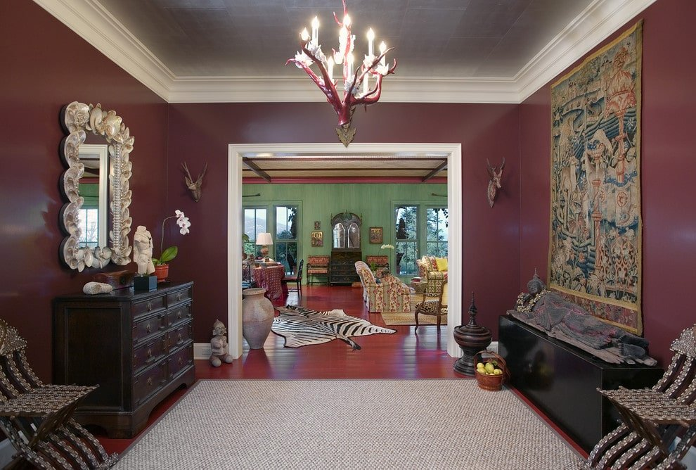 Various decors run throughout this spacious foyer with burgundy walls and rich hardwood flooring topped by a gray rug. It offers a dark wood divan and facing eccentric chairs along with a dresser that's paired with a gorgeous white mirror.