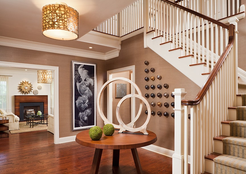 A drum semi-flush mount light illuminates this eclectic foyer showcasing rectangular artwork and various round decors on a wooden table along with metal sphere art mounted against the traditional staircase that's covered in a striped runner.