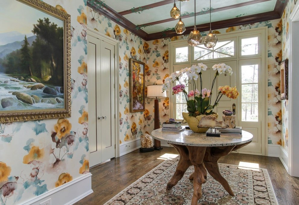 Clad in gorgeous floral wallpaper, this foyer showcases large artworks and exquisite pendant lights that hung over the stump center table. It sits on a patterned area rug over the natural hardwood flooring.