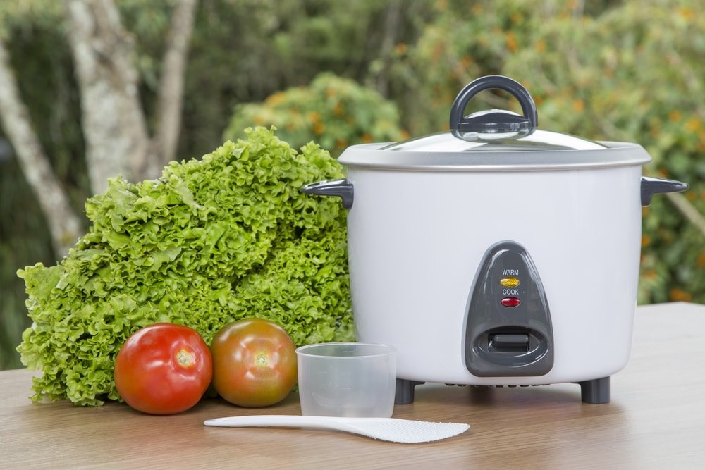 Electric rice cooker on a wooden desk with a measuring cup, rice spoon, a pair of tomatoes, and lettuce.