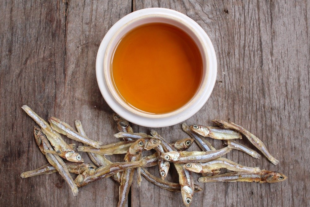 Fish sauce on a bowl beside some dried fish.