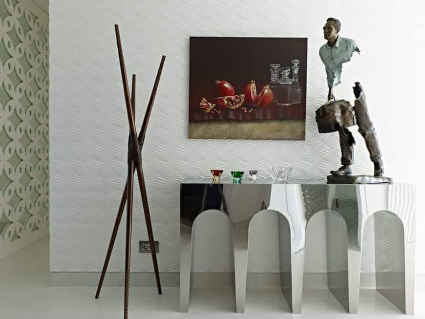Interesting foyer with eclectic decors showcasing dark wood sticks and a gorgeous painting mounted on the white wall.  It includes a man sculpture and glass bowls in various colors that sit on a mirrored console table designed with arches.
