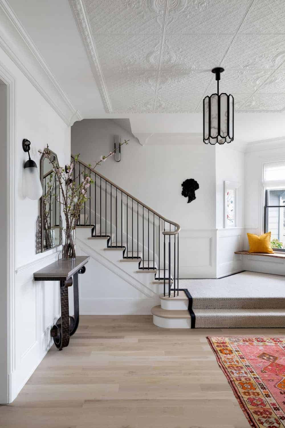 Victorian foyer illuminated by a wrought iron pendant light that hung from the ornate white ceiling. There's a metal console table on the side that's paired with a gorgeous mirror along with a bordered area rug on the opposite side that lays on the natural hardwood flooring.