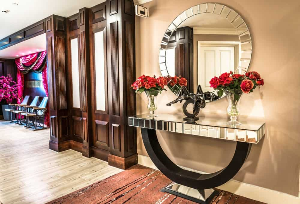 Elegant foyer decorated with a large, round mirror that hung above a matching console table over a brown area rug. It is topped with glass flower vases and a gorgeous bronze sculpture.
