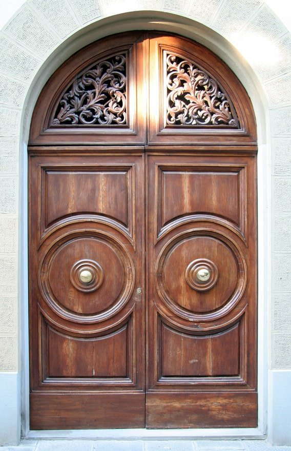 Another classic wooden door in arched that's accented with intricate carvings and trims. A pair of brass knobs complete the look.