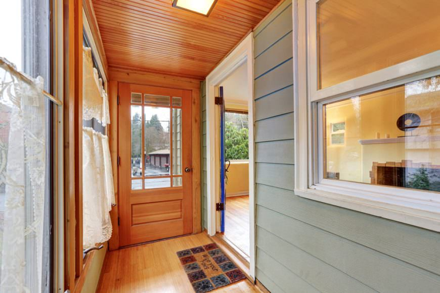 A simple glazed front door that blends in with the hardwood flooring and wood plank ceiling fitted with a skylight.