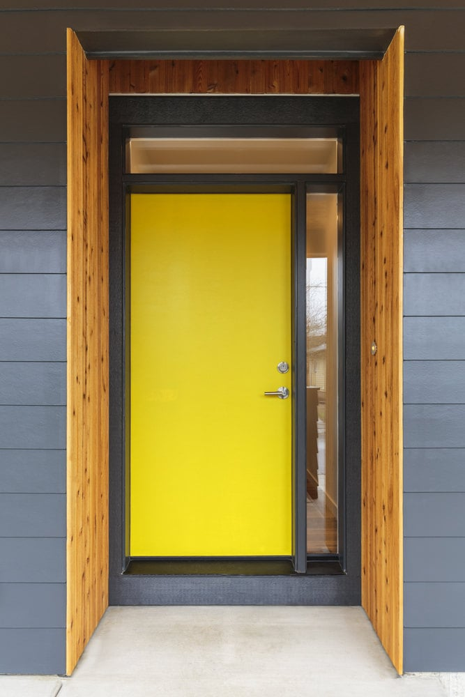 A yellow front door with a side glass panel and a transom window. Its vibrant color makes it stand out against the gray walls regardless of its plain design.