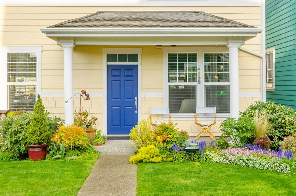 A straight pavement sandwiched by lush green lawns leads to the blue front door on an open porch lined with white columns. It is complemented by folding chairs situated against the light yellow walls.