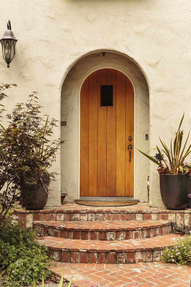 Arched front door illuminated by a glass sconce that's mounted on the concrete wall. It is accompanied by a brown rug flanked by large potted plants along with entry stairs that are arranged in a herringbone pattern.