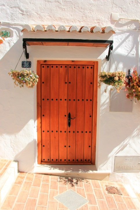 A wood plank door on a Greek house with iron details adorned by lovely hanging plants that are fixed under the roof.