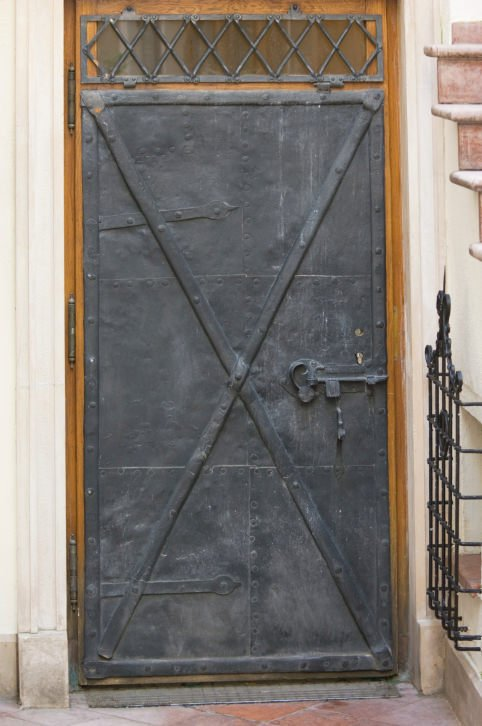 A metal front door with a rustic look showcasing an x-trim and a transom window against the wooden background.