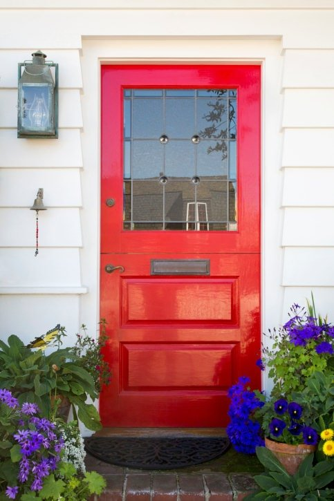 A classic red door that truly stands out. It is fitted with a charming bronze handle and plate matching with the glass sconce and small bell that are mounted on the white siding.
