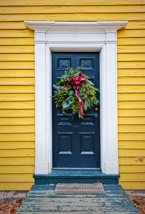 Cheerful yellow sidings add a striking contrast to the deep blue front door that matches the walkway. It is adorned by a charming wreath surrounded by white trims.