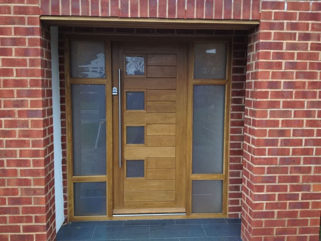 Red brick walls set a textured backdrop to the wooden front door that's flanked by frosted glass panels. It is fitted with small glass insets and a long chrome handle matching with the door lock.