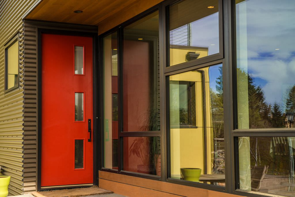 A sleek red door with glass insets and a wrought iron handle stands out in this modern house showcasing gray sidings and glass paneled windows.
