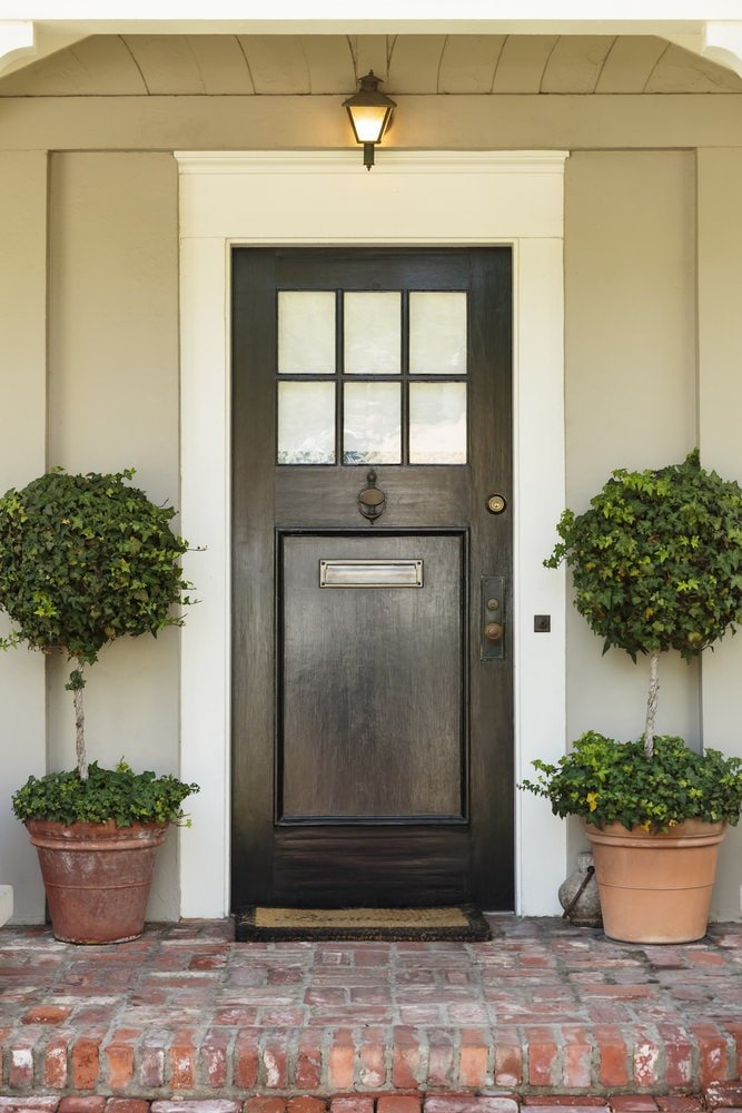 A pair of manicured shrubs flanked the black door that's contrasted by a white surround. It is illuminated by a warm sconce that's fixed under the shiplap ceiling.