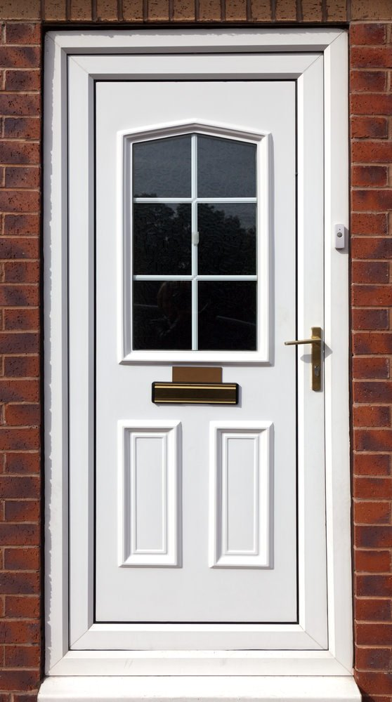 A white front door that stands out against the red brick walls. It is fitted with a framed glass inset along with a brass handle and plate.