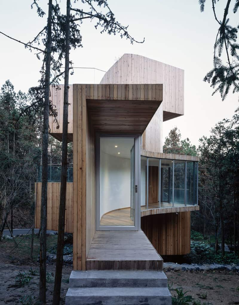 A lumber house showcasing parallel wood planks and curved glazing. It includes concrete entry stairs leading to a wooden landing with a glass front door framed in aluminum.