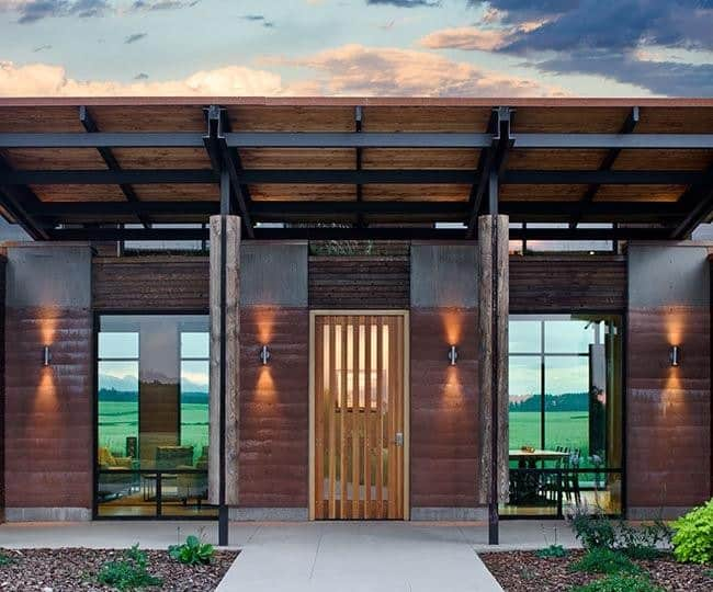 A wood slat front door flanked by sleek sconces and glazed windows framed in black aluminum. It is lined with a pair of columns that are situated in front of the tiled walkway.
